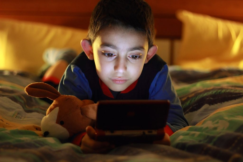 kid in bed wih videogame console on night